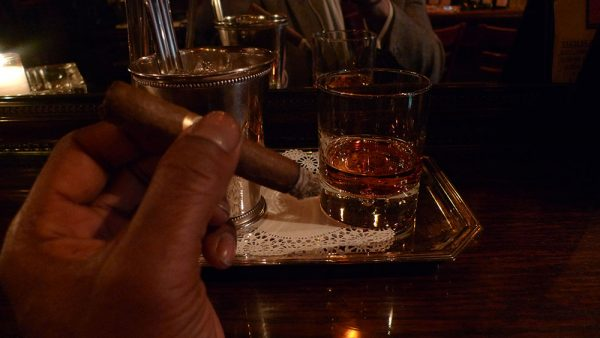Glass of bourbon with cigar in hand